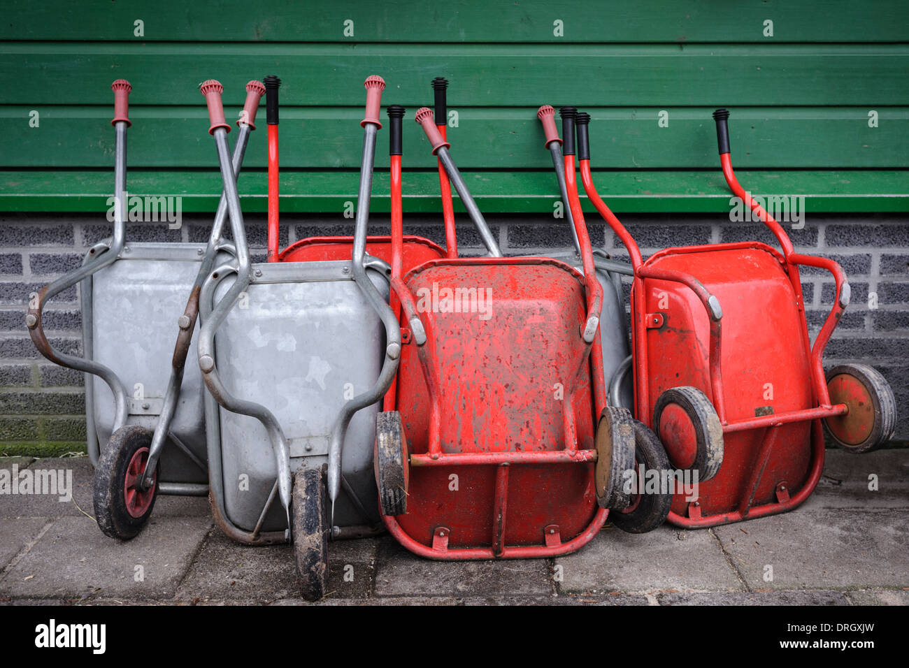 Wheelbarrows leaning against a wall, Noord Holland, Netherlands - Stock Image
