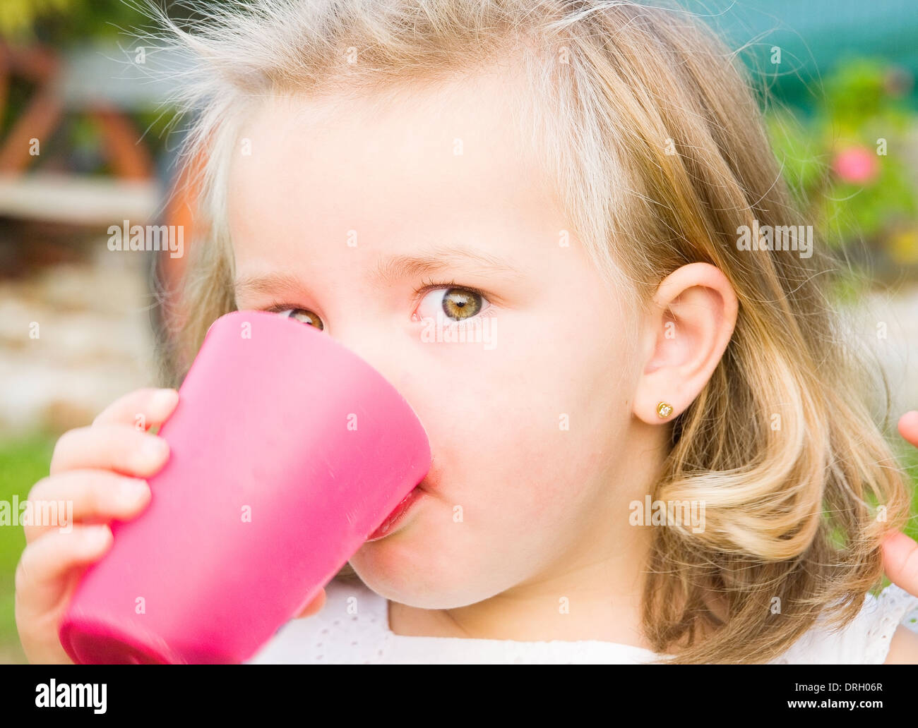 Little girl drinking, The girl is looking at camera. - Stock Image