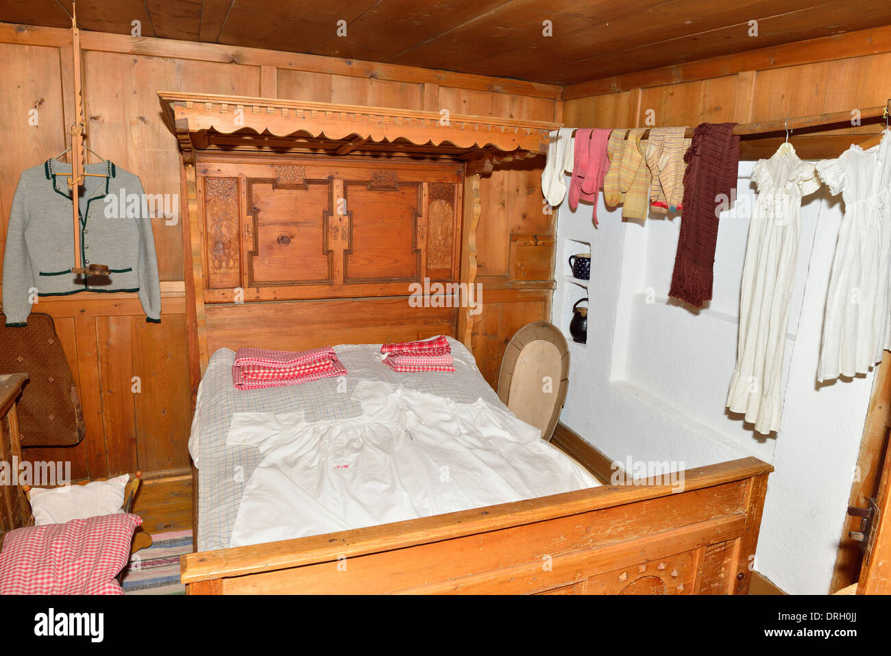 Typical bedroom in a traditonal Bavarian house with wood for panels, bed ,room furniture  with clothes hung to dry in same room - Stock Image