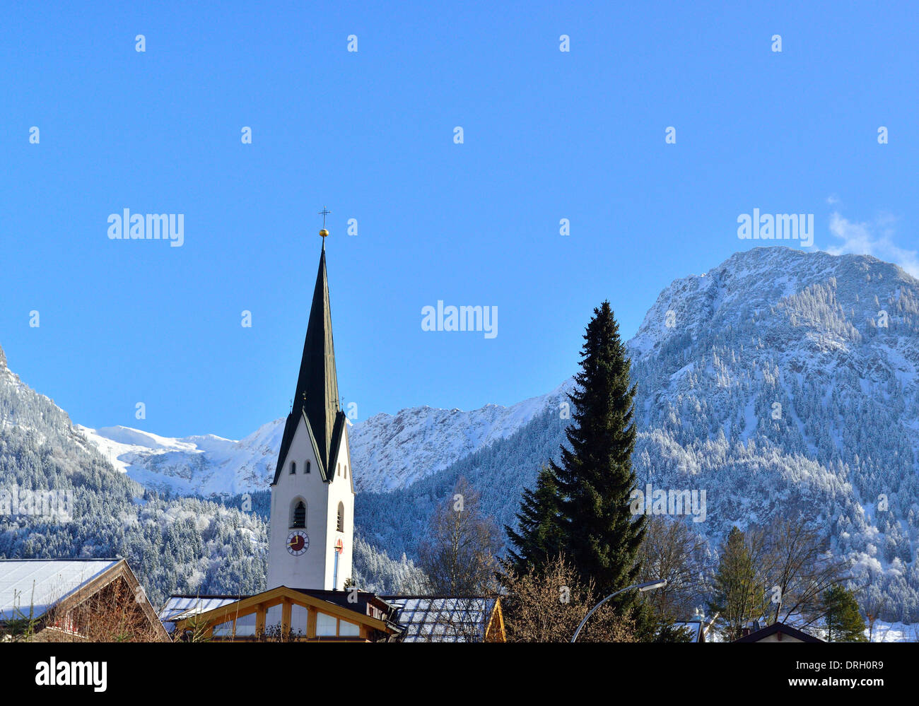 Oberstdorf in winter with a snow fall looking towards  St. Johann Baptist church and  the Bavarian  Alps foothills behind - Stock Image