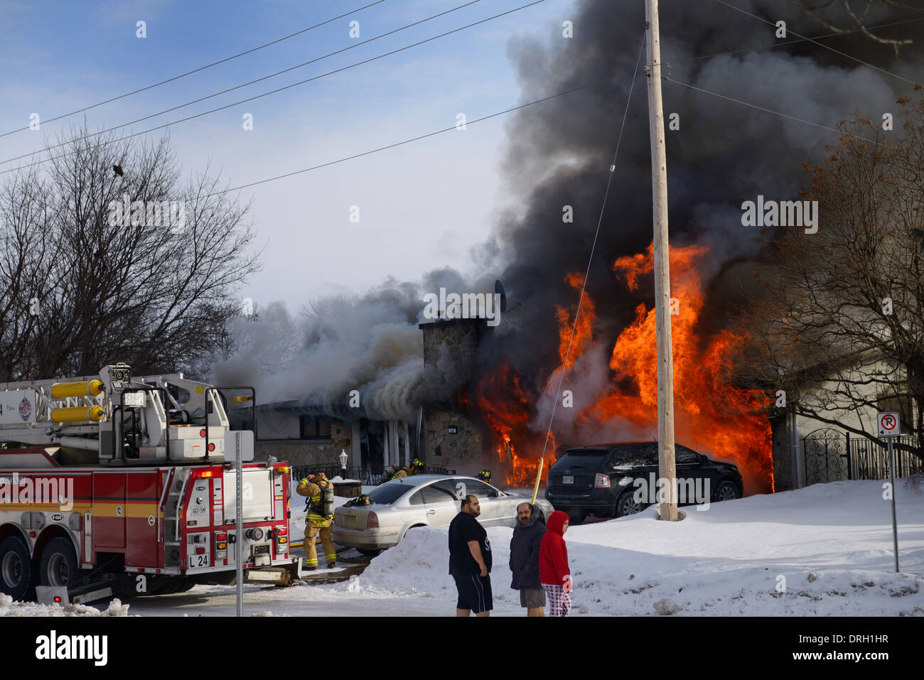 Residents outside in night clothes in winter with snow while house goes up in flames with firefighters spraying water on fire in Ottawa - Stock Image