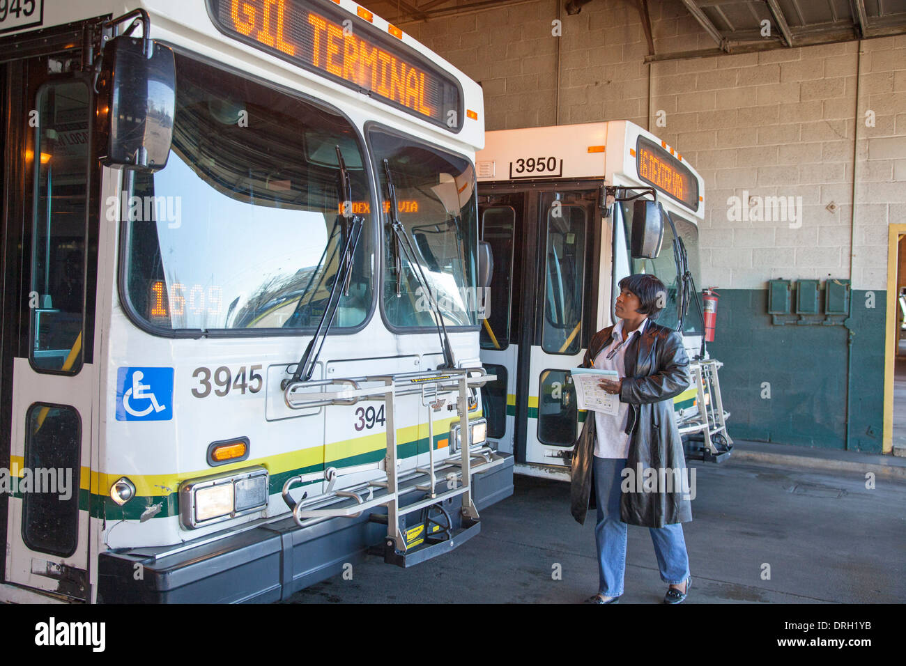 A worker checks on the condition of city buses at a Detroit bus terminal. - Stock Image