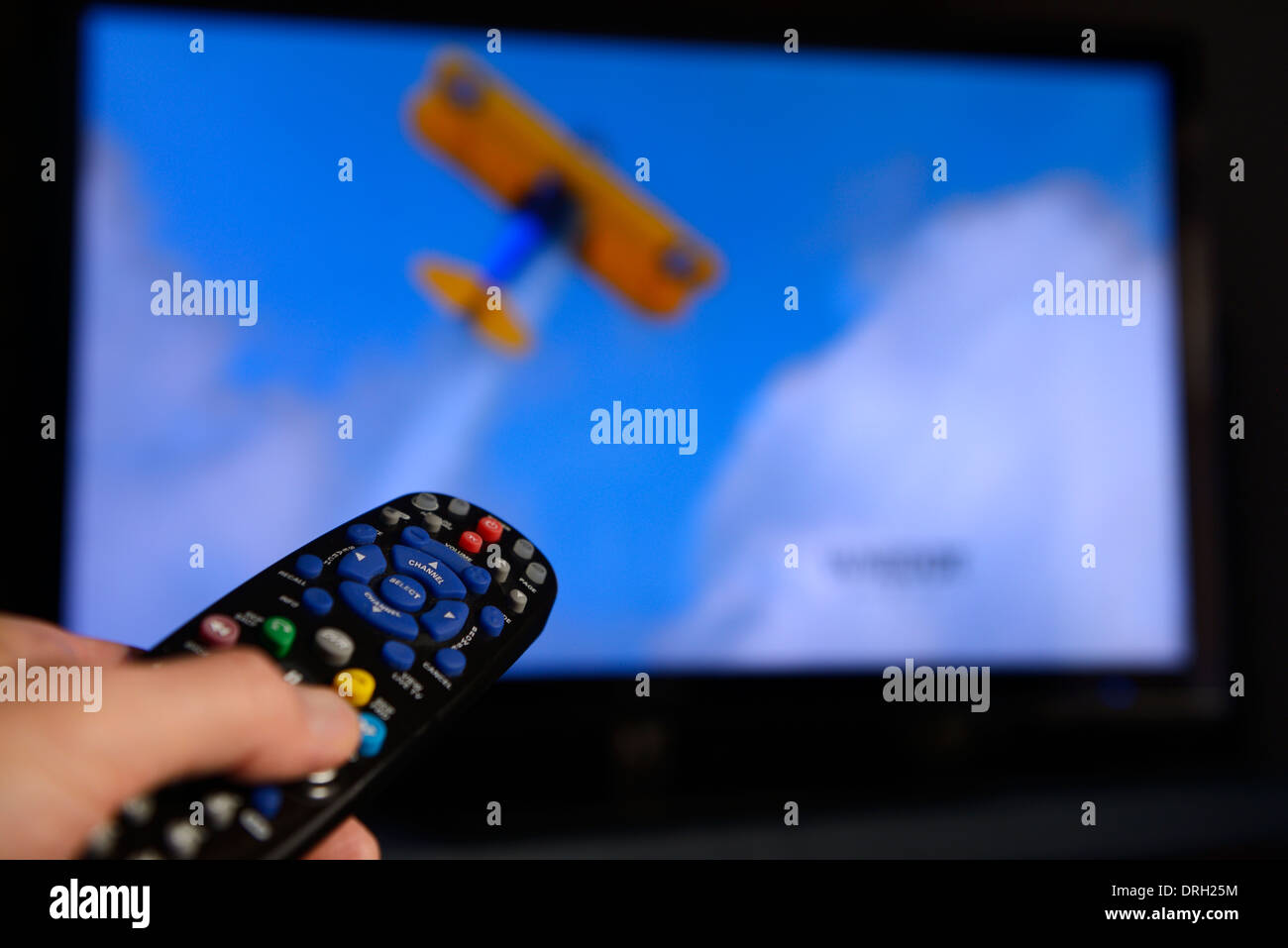 Man pointing a universal remote control towards a television screen to change the program on the entertainment system - Stock Image