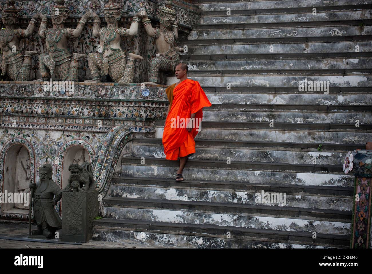 Monk descending the stairs at Wat Pho in Bangkok Thailand - Stock Image