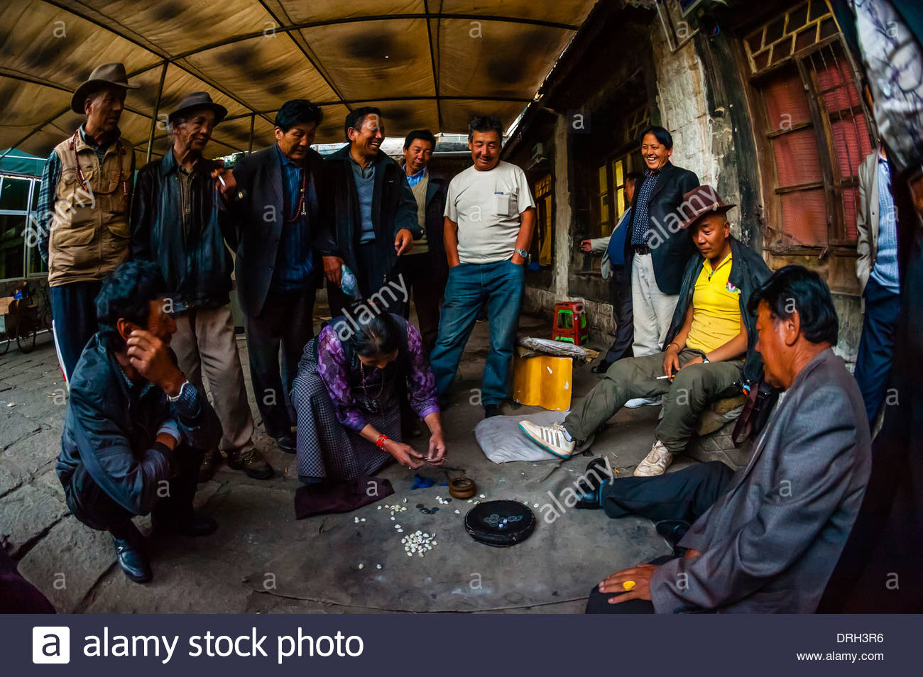 People gambling on a back street in Old Lhasa, Tibet (Xizang), China. - Stock Image