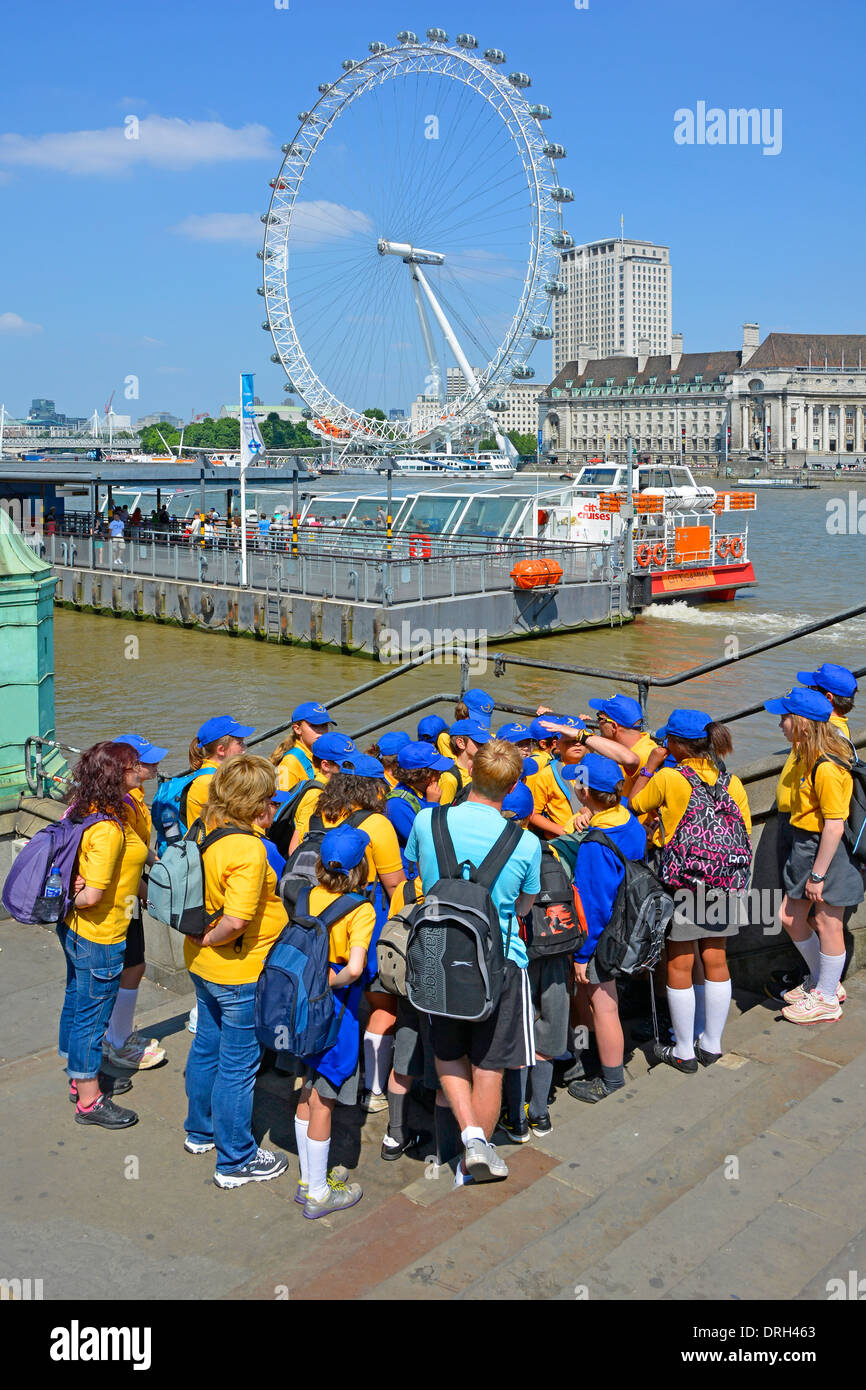 Children in colourful school uniform with teachers beside River Thames - Stock Image