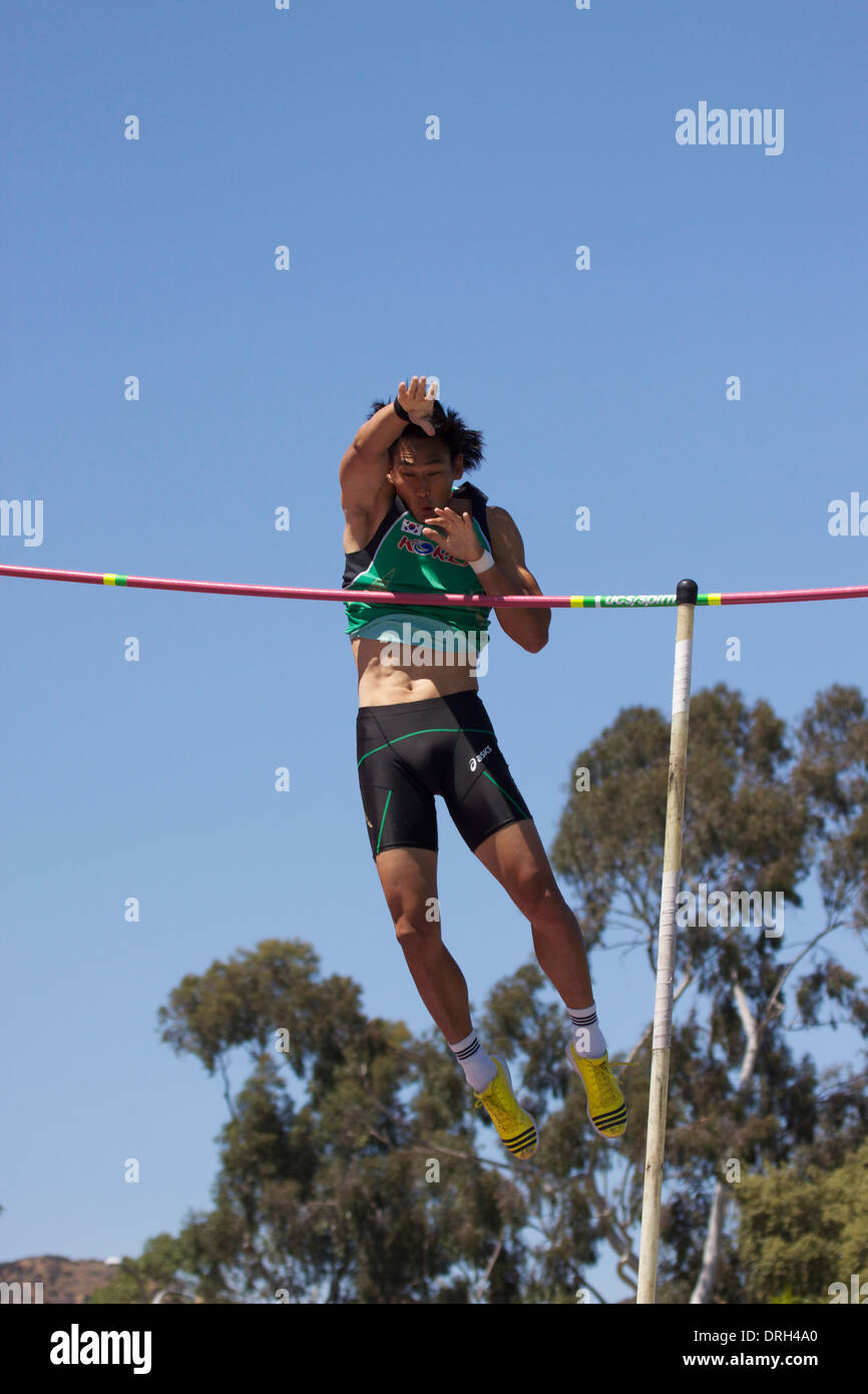 Korean Pole Vaulter clears the bar during a track and field meet in Southern California - Stock Image
