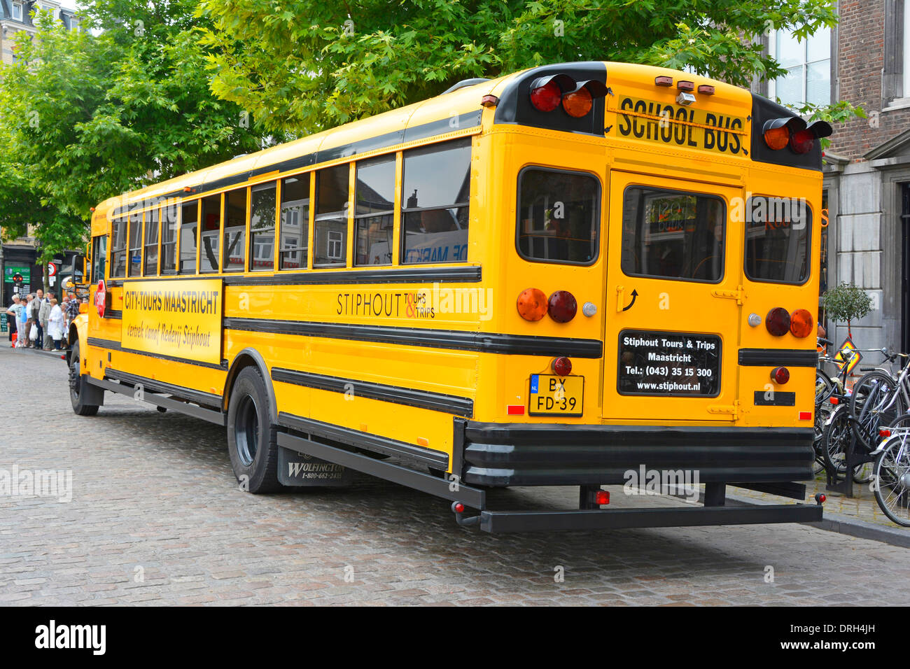 Yellow American school bus adapted for city sightseeing tours of Maastricht Limburg Netherlands Holland - Stock Image