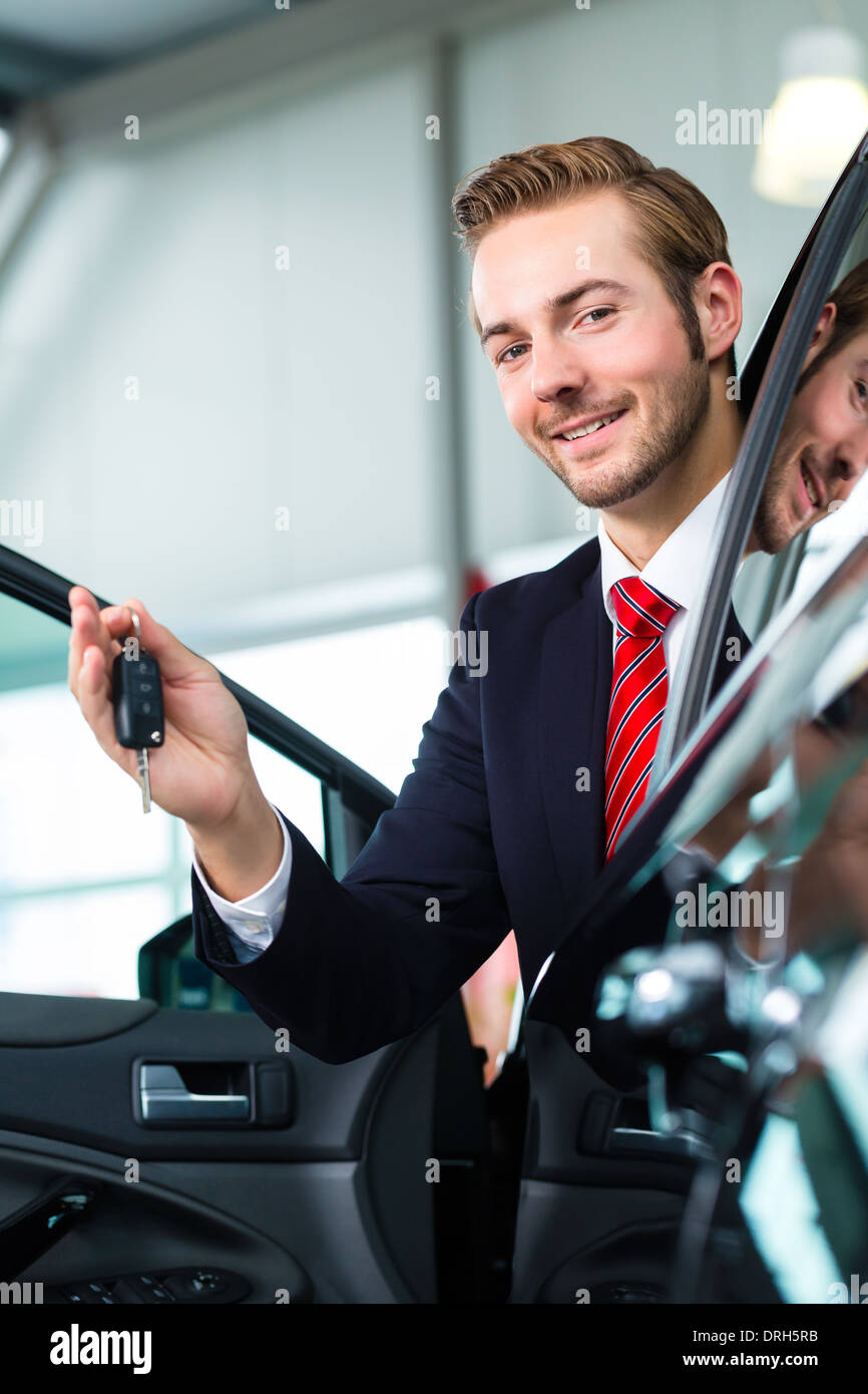 Seller or car salesman in car dealership with key presenting his new and used cars in the showroom - Stock Image
