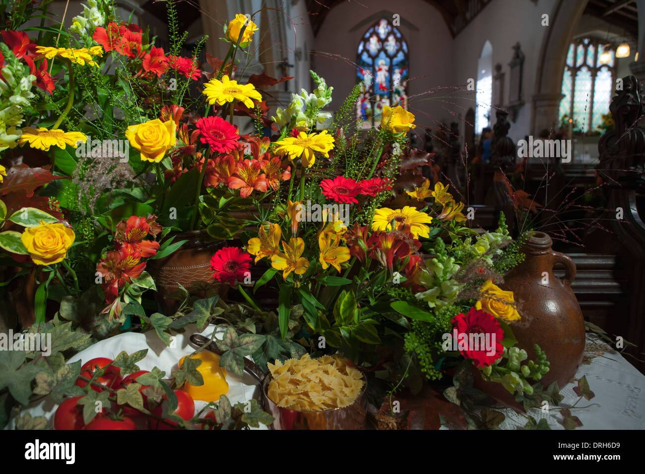 Italian themed flower arrangement in English country church at Harvest festival - Stock Image