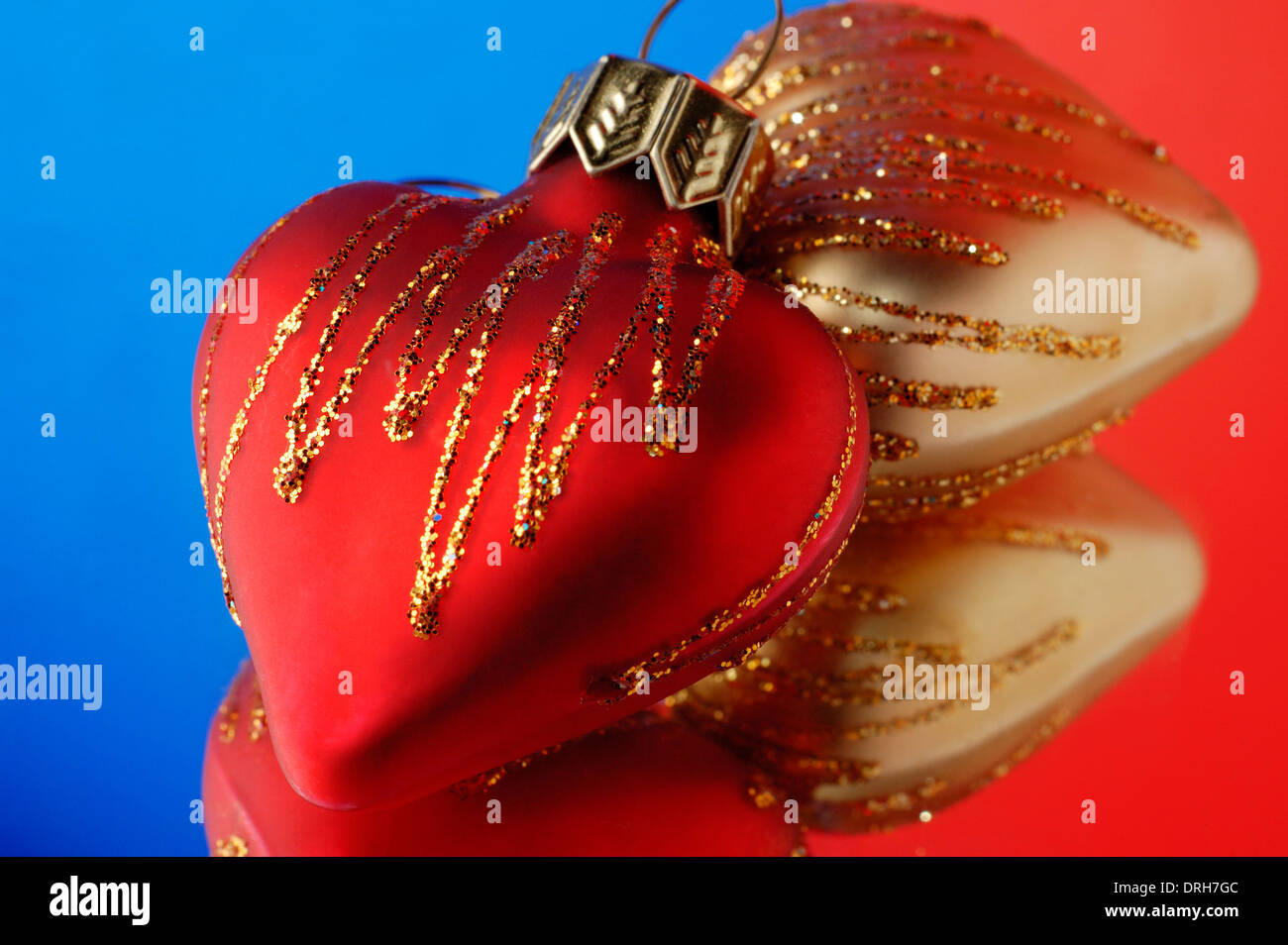 two heart shaped christmas ornaments on blue red background stock