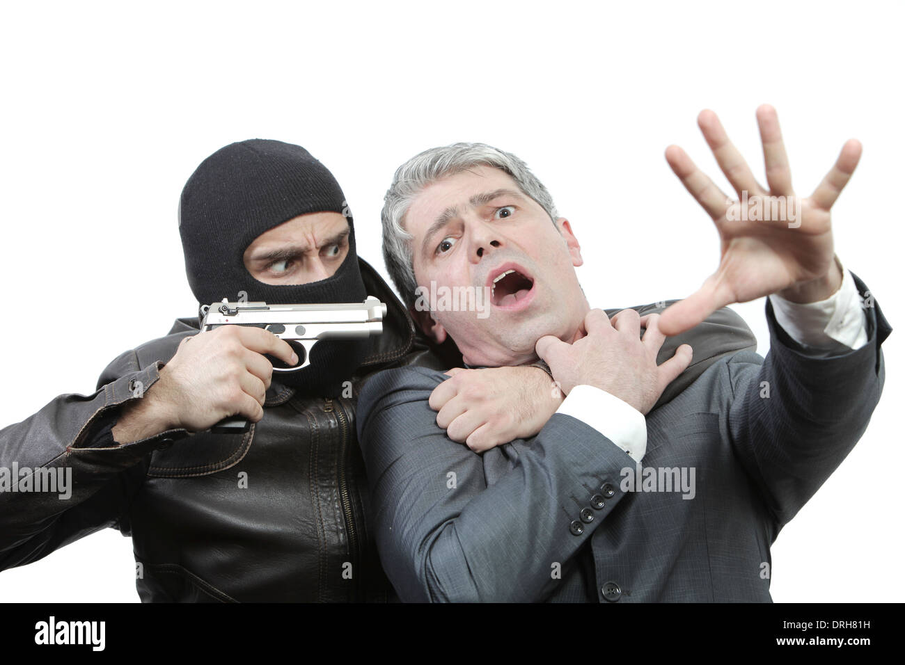 Kidnapper threatening a businessman with a gun... - Stock Image