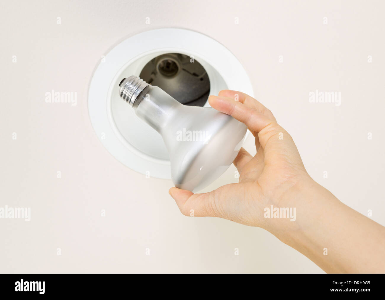 Photo of burned out flood light bulb being held by female hand with recessed ceiling light mount in background - Stock Image
