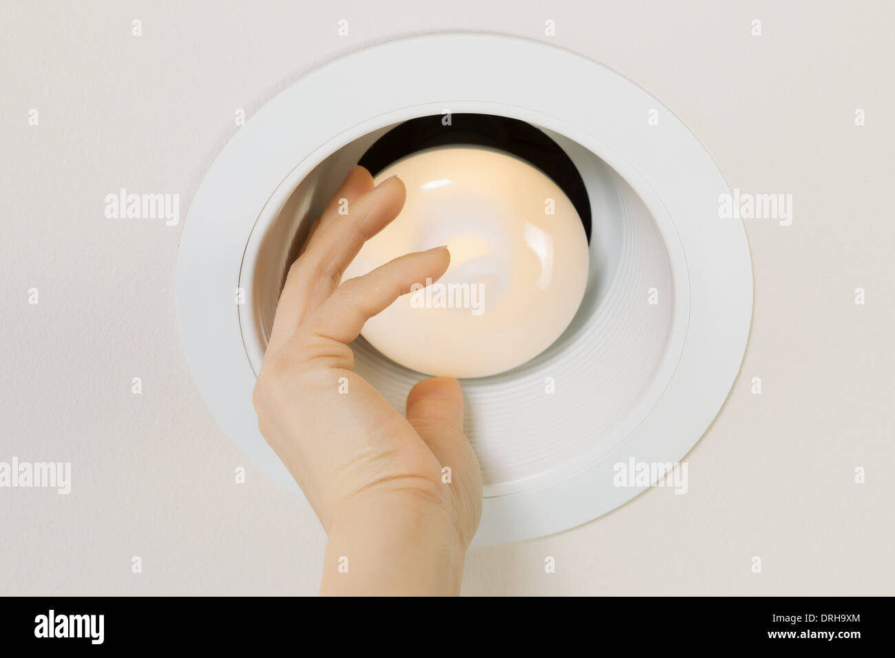 Photo of brand new illuminated flood light bulb being screwed in by female hand with recessed ceiling light mount in background - Stock Image