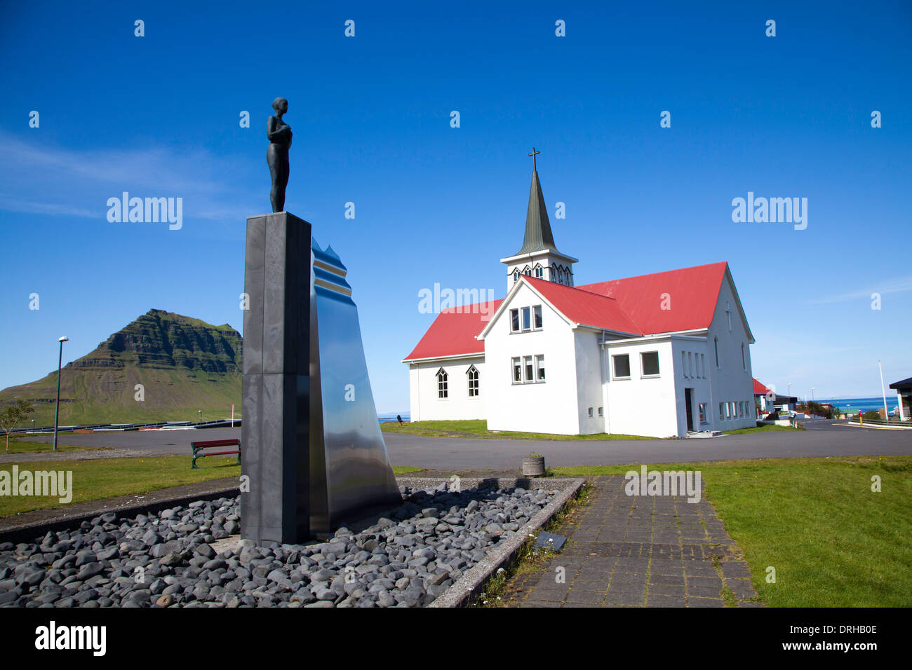 The modern 1961 church in Grundarfjordur, Iceland. The sculpture in the foreground is called 'Syn'. - Stock Image
