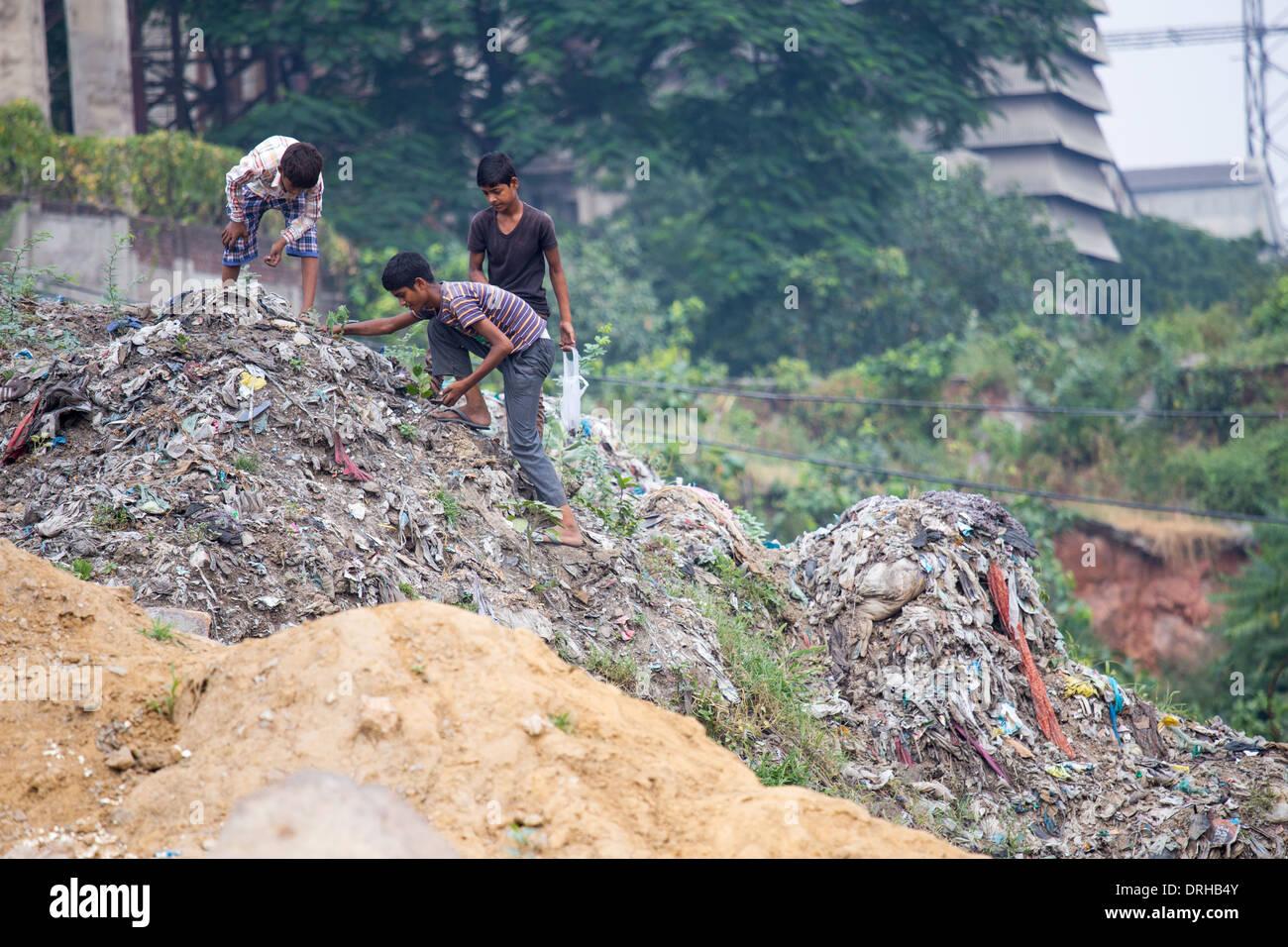 Boys picking through a landfill in Delhi, India - Stock Image