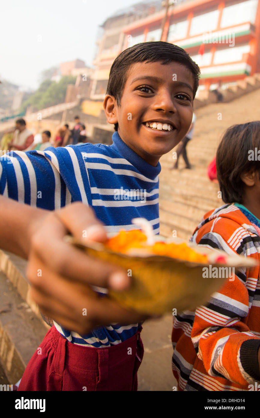 Boy offering flowers for the puja in Varanasi, India - Stock Image