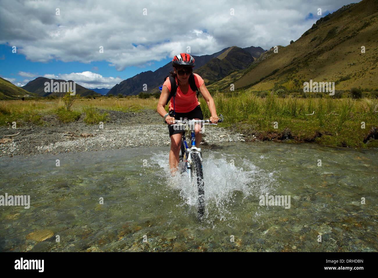 Mountain biker crossing Moke Creek, near Queenstown, Otago, South Island, New Zealand - Stock Image