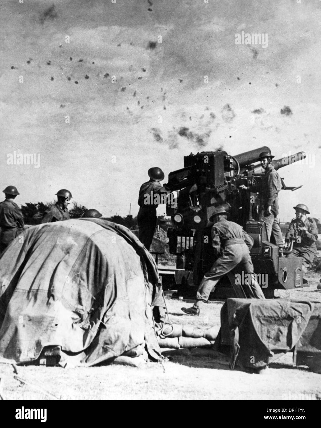 British gunners at work beneath a flak-filled sky, WW2 - Stock Image
