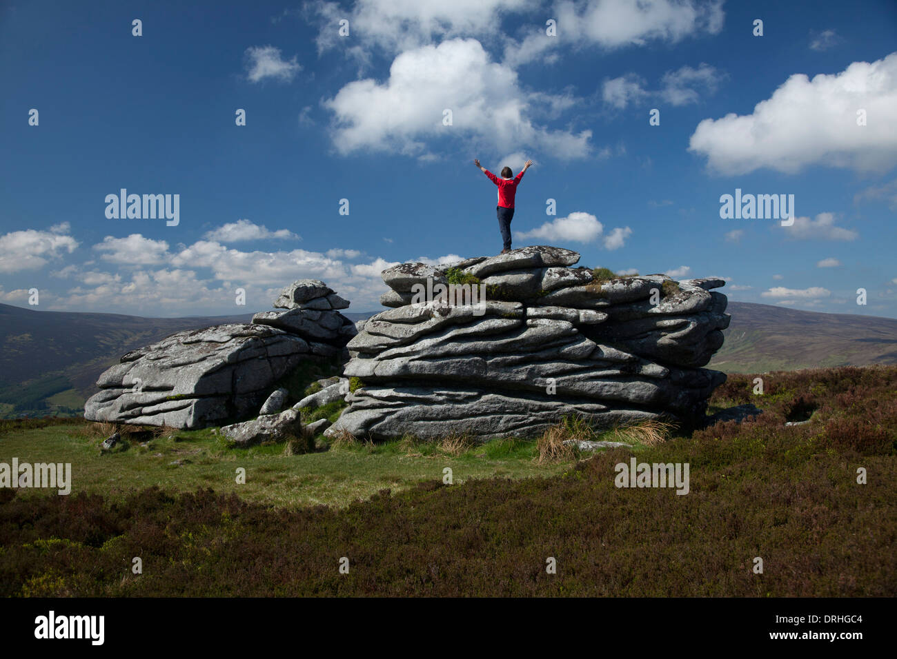 Walker on the granite tor of Fitzwilliam's Seat, near the summit of Knocknagun. On the border of counties Dublin and Wicklow, Ireland. - Stock Image