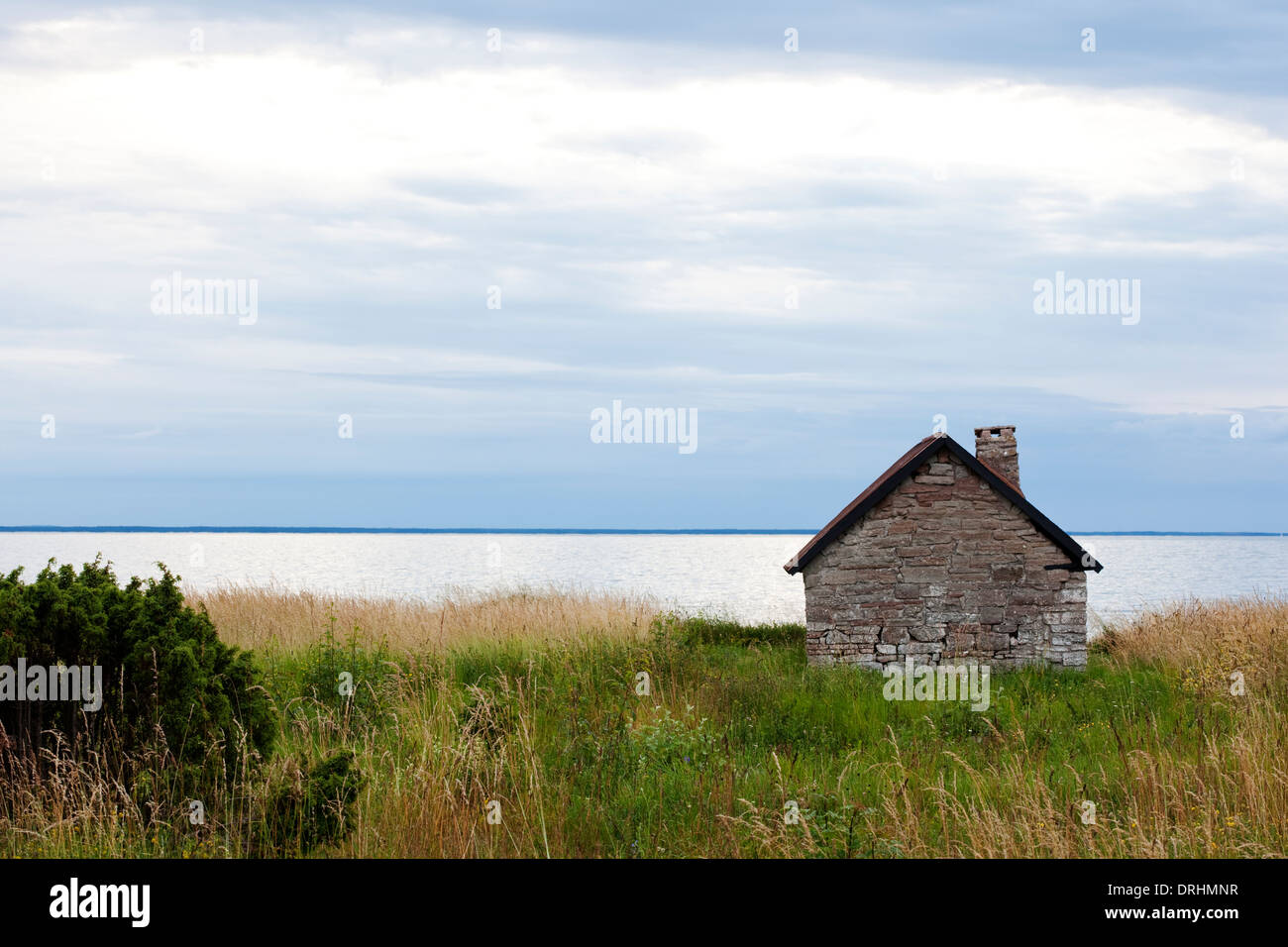 Field with blurred house and shoreline in background.Djupvik,Öland.Sweden - Stock Image