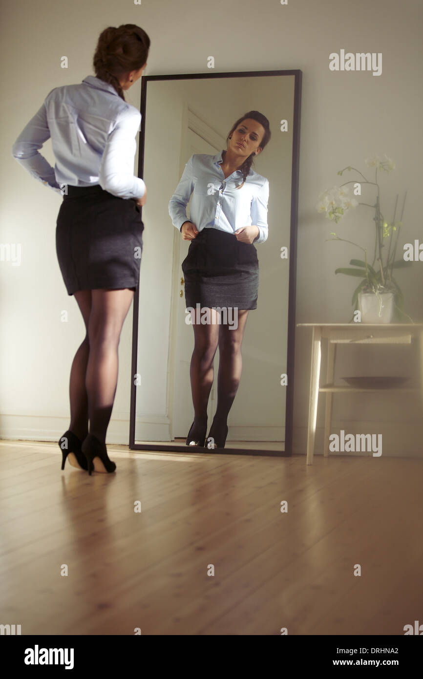 Young businesswoman checking herself in the mirror. Beautiful caucasian female model in business attire getting - Stock Image