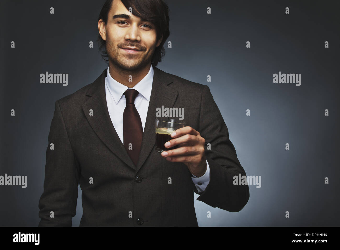 Portrait of happy young business man offering you a cup of coffee against black background. Mixed race male model - Stock Image