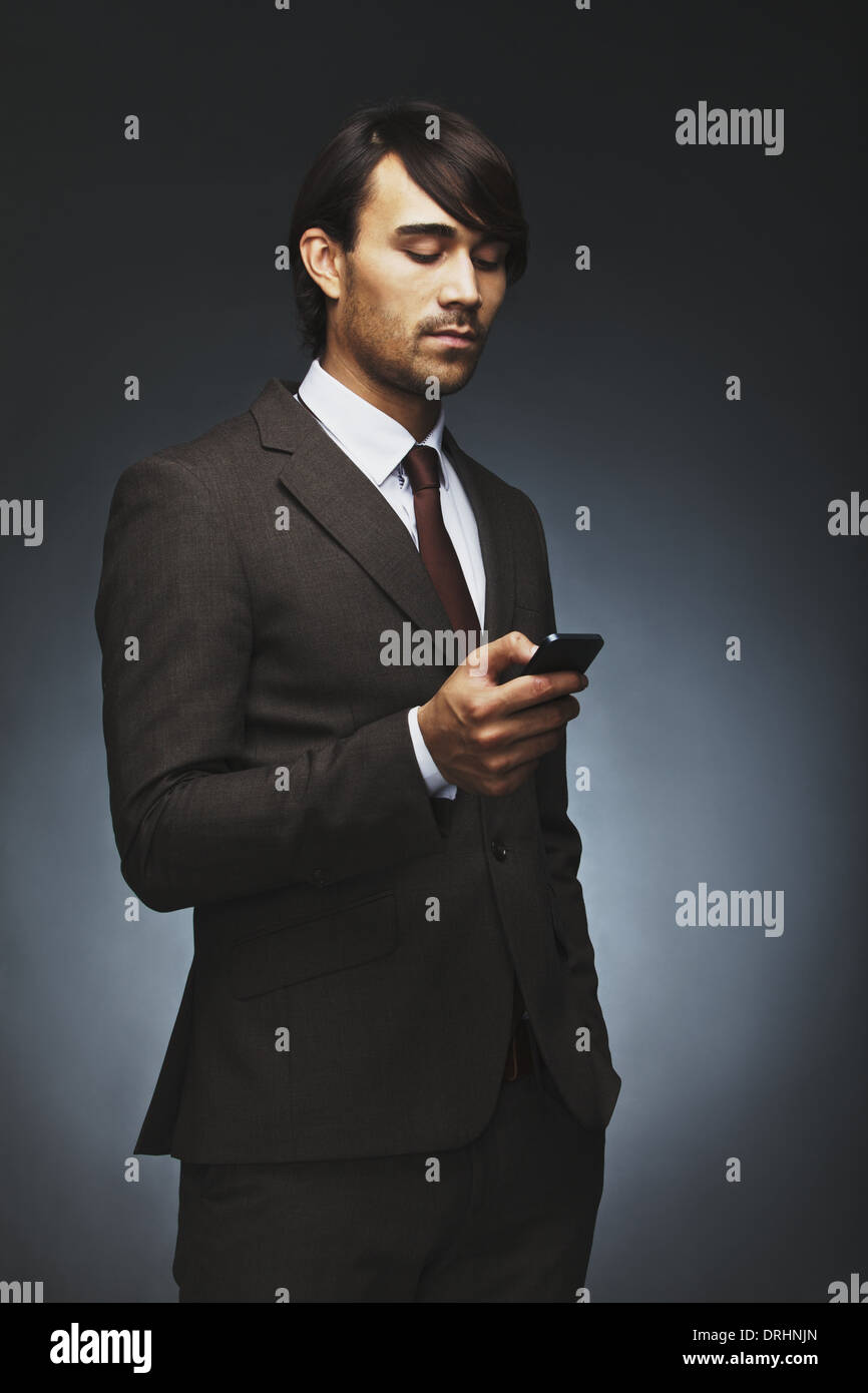 Handsome young businessman reading text message on his smart phone. Mixed race male model in business suit using mobile phone. - Stock Image