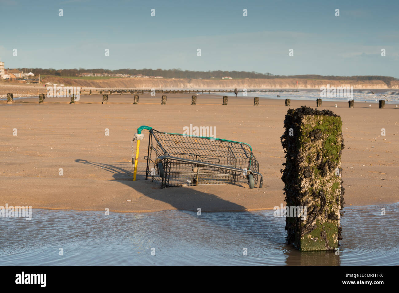 An abandoned supermarket trolley on the beach in Bridlington - Stock Image