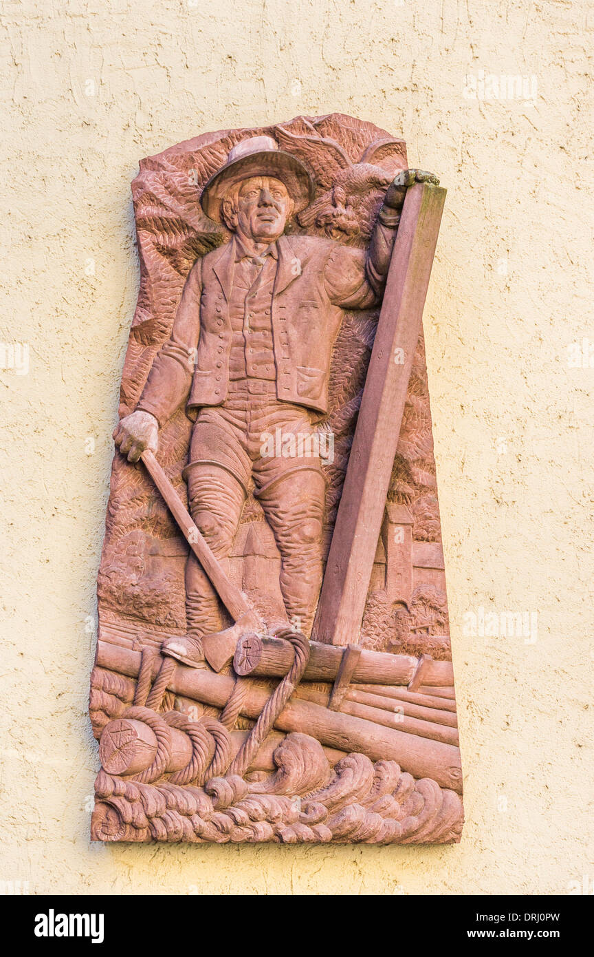 relief on the facade of a building showing a black forest rafter rafting logs on a river, wolfach, black forest - Stock Image