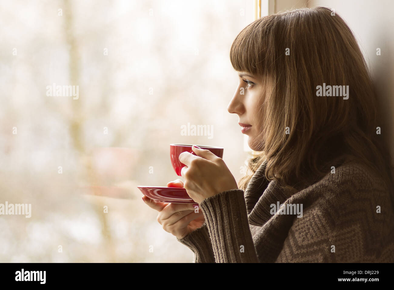 Beautiful girl drinking Coffee or Tea near Window - Stock Image