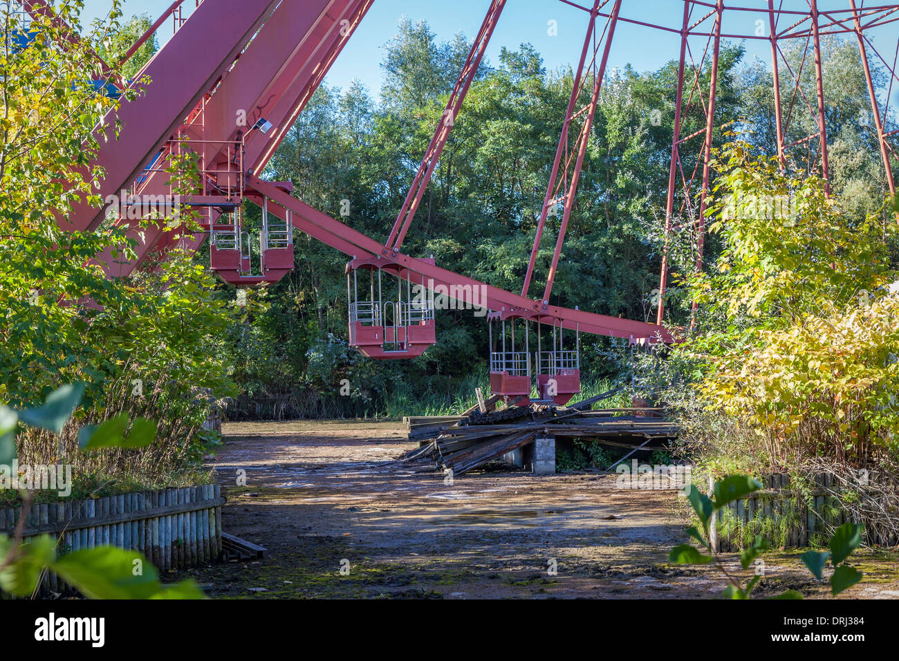 Old, disused, derelict ferris wheel above slimy, murky pond at the abandoned amusement park Plånterwald, Berlin - Stock Image
