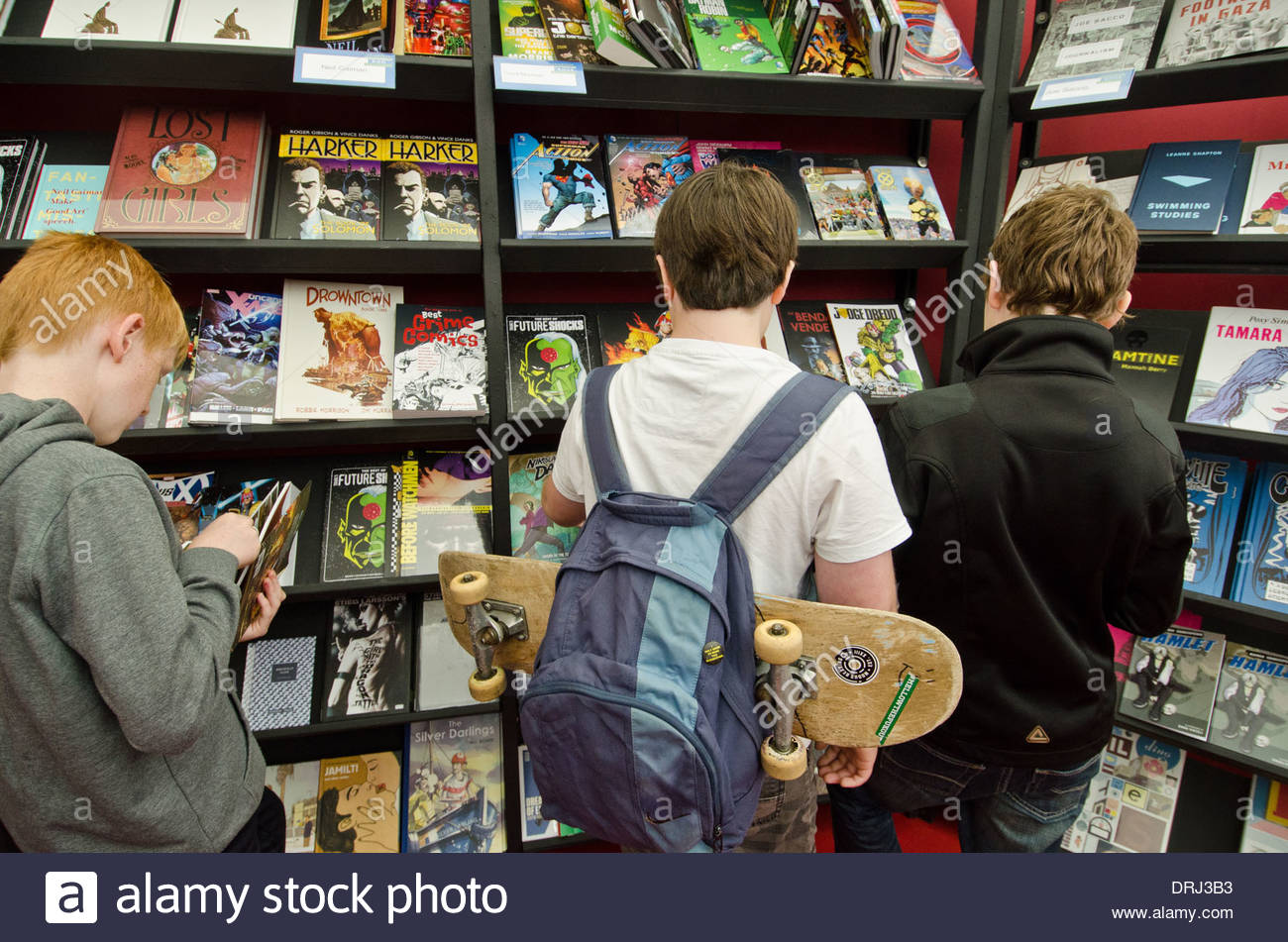 Young visitors of the Edinburgh International Book Festival browse comic books in the 'bookshop tent' - Stock Image