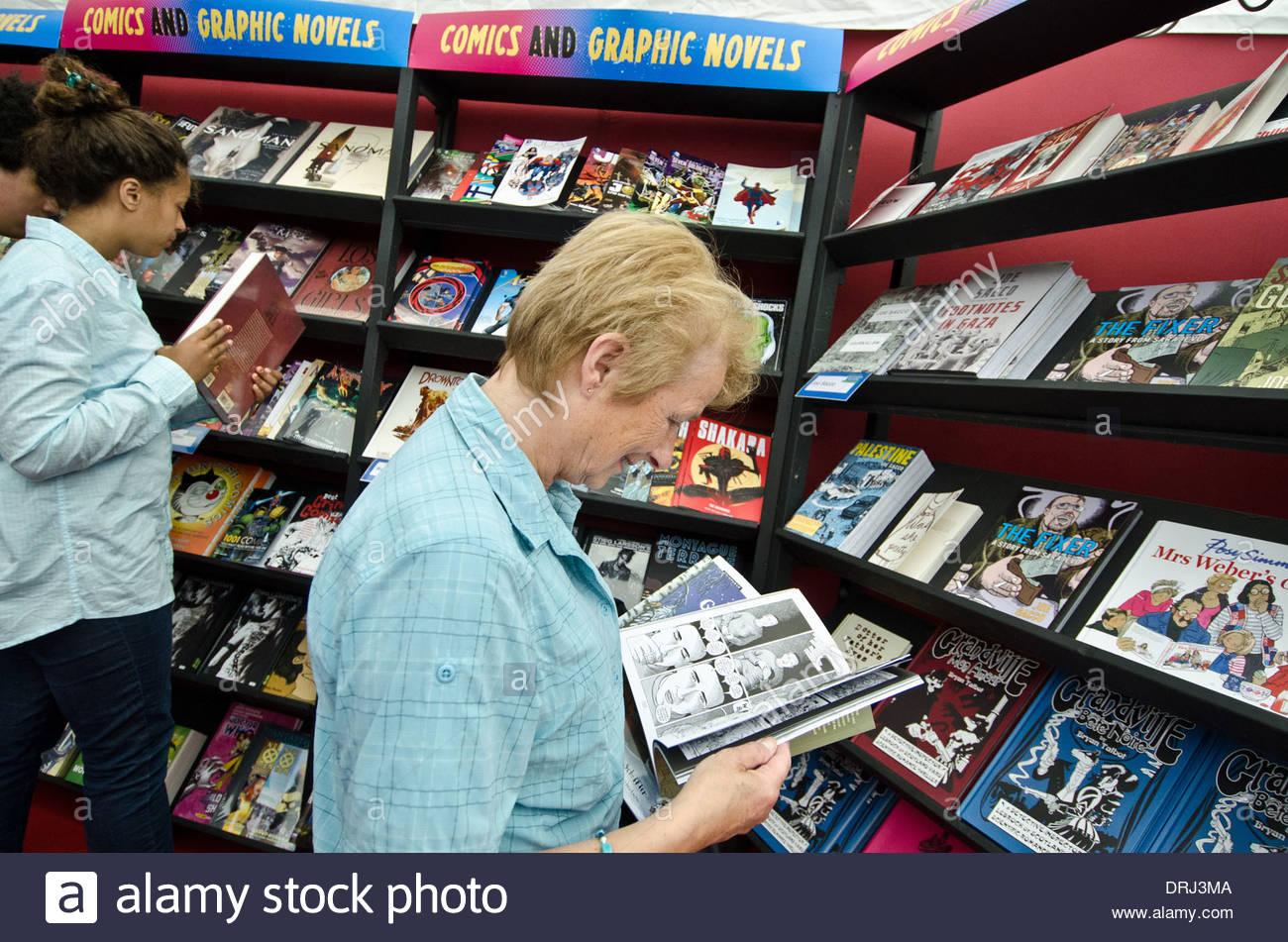 Visitors of the Edinburgh International Book Festival browse comic books in the 'bookshop tent' - Stock Image