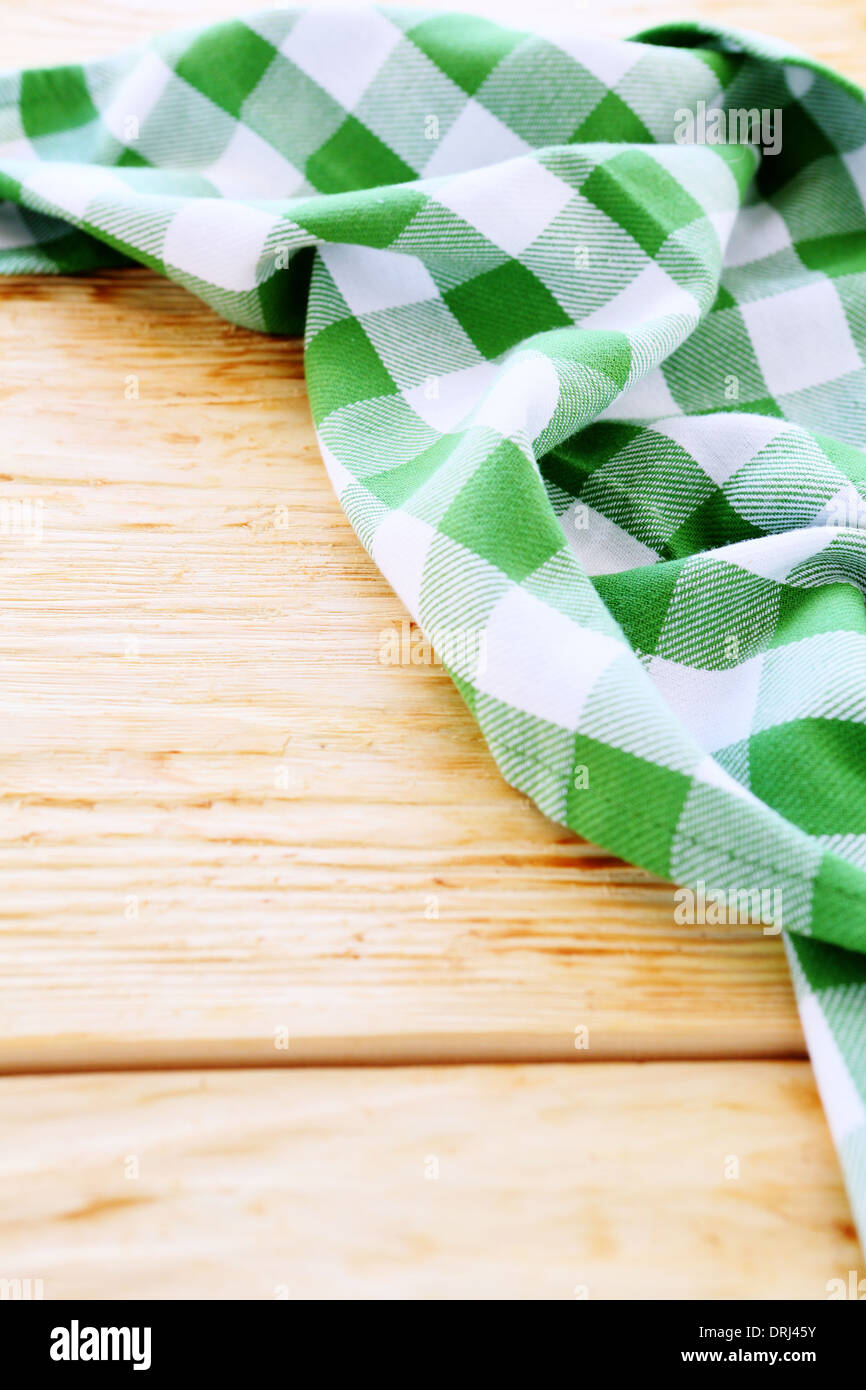wooden table covered with green tablecloth - Stock Image
