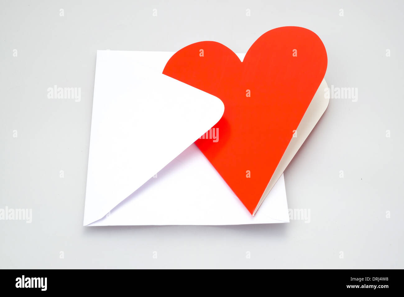 Perfect for a love letter, a heart shaped greeting card and envelope - studio shot with a white background - Stock Image