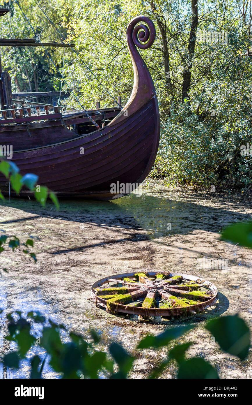 Rusting pirate ship and old wheel on slimy pond at abandoned amusement  park, Spreepark, Plånterwald, Treptow-Kopernick, Berlin