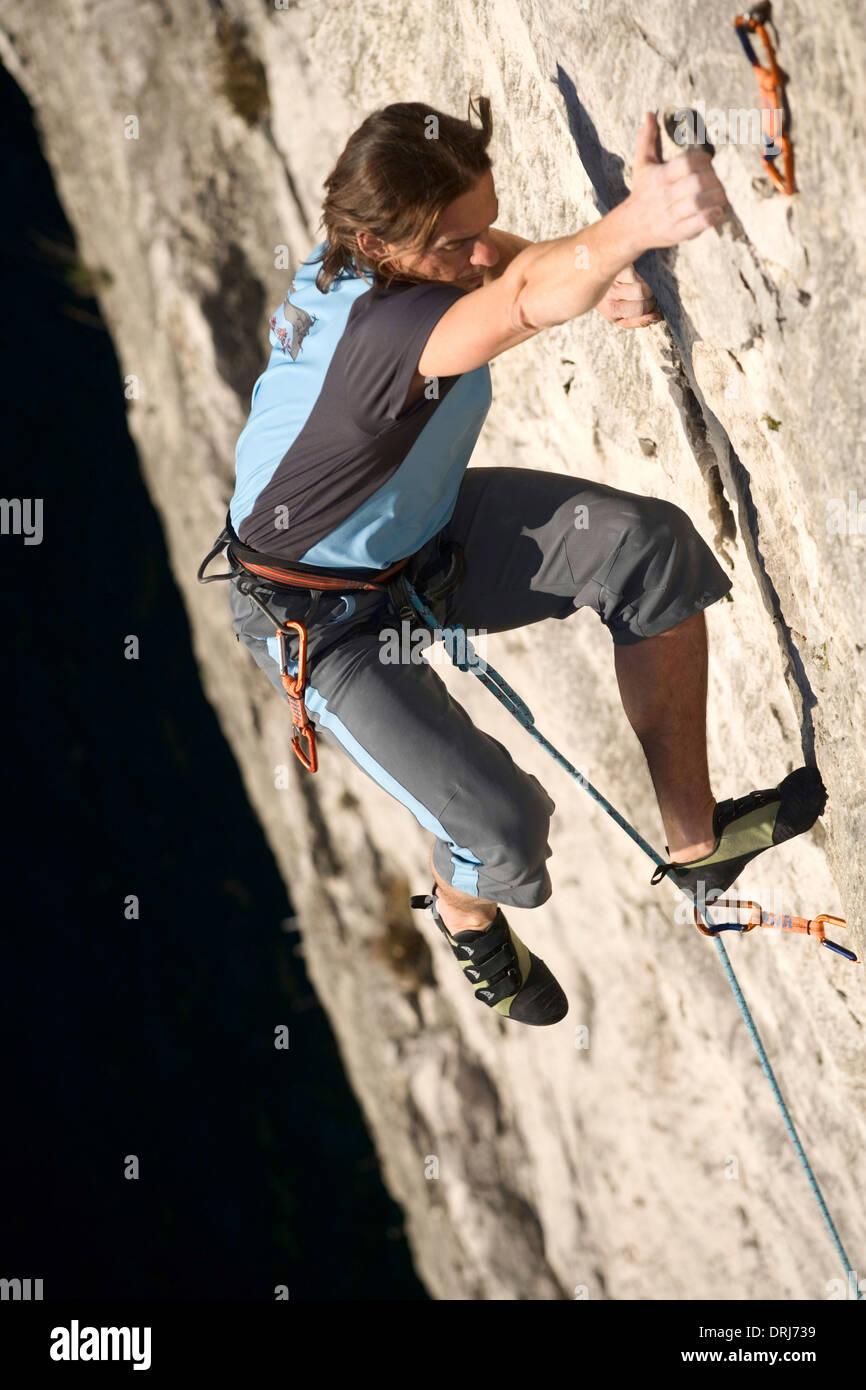 Man climbs rock face up, Mann klettert Bergwand hinauf Stock Photo
