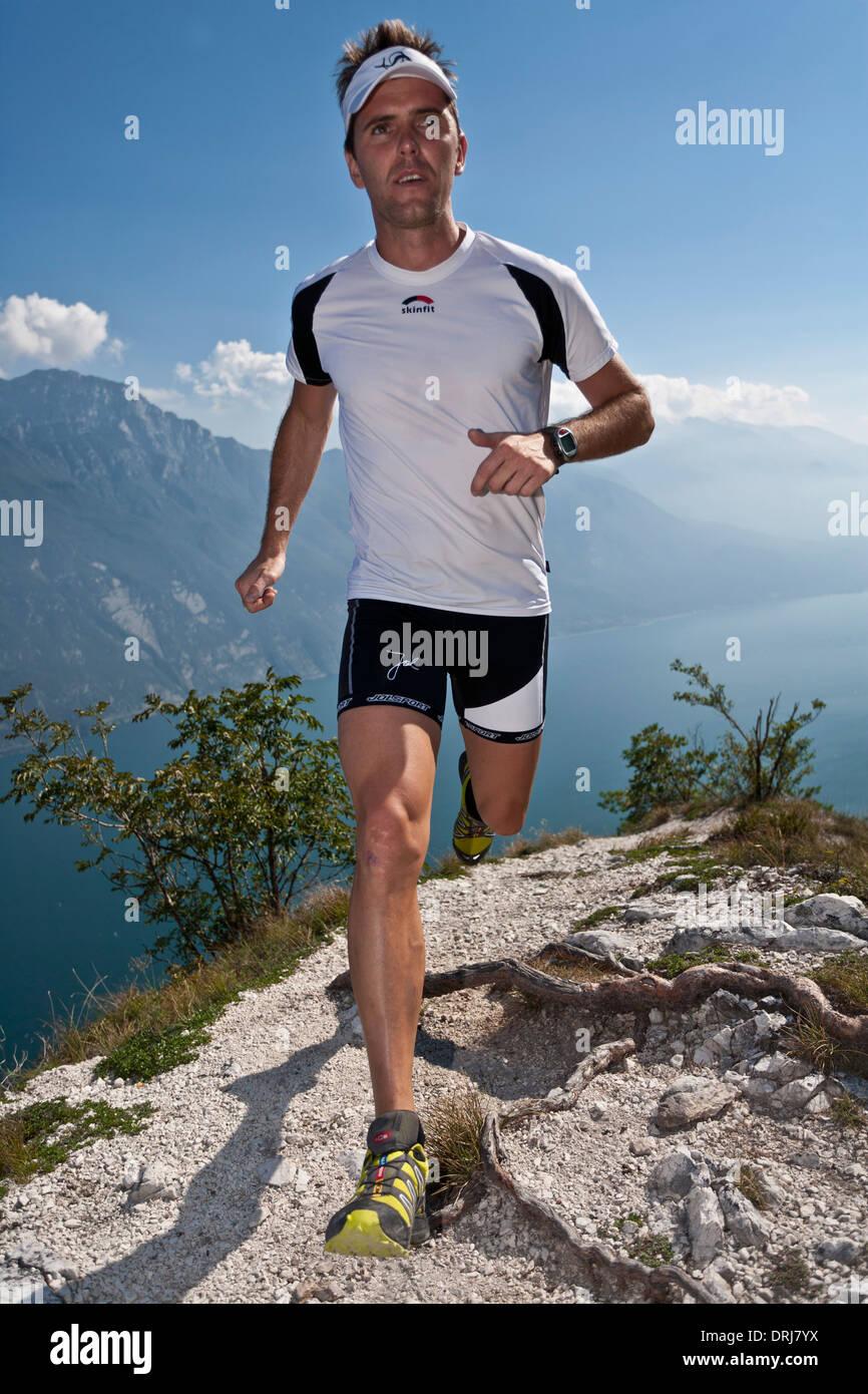 Man runs through the mountains in the Gardasee, Mann laeuft uebers Gebirge am Gardasee - Stock Image