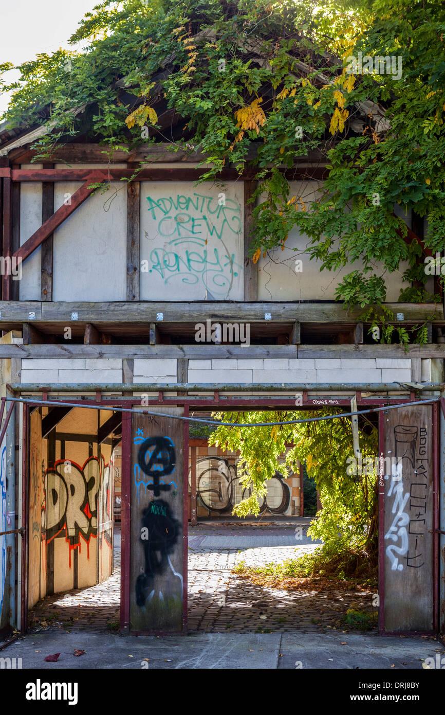 Damaged, creeper and graffiti covered, derelict English village building,  Spreepark, Plånterwald, Treptow-Kopernick, Berlin - Stock Image
