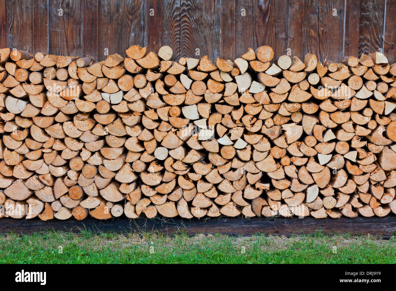Stack of split firewood used as wood fuel stored against wooden cabin - Stock Image
