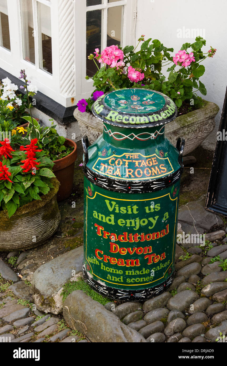 Old painted milk churn outside the tearooms in Clovelly, Devon Stock Photo
