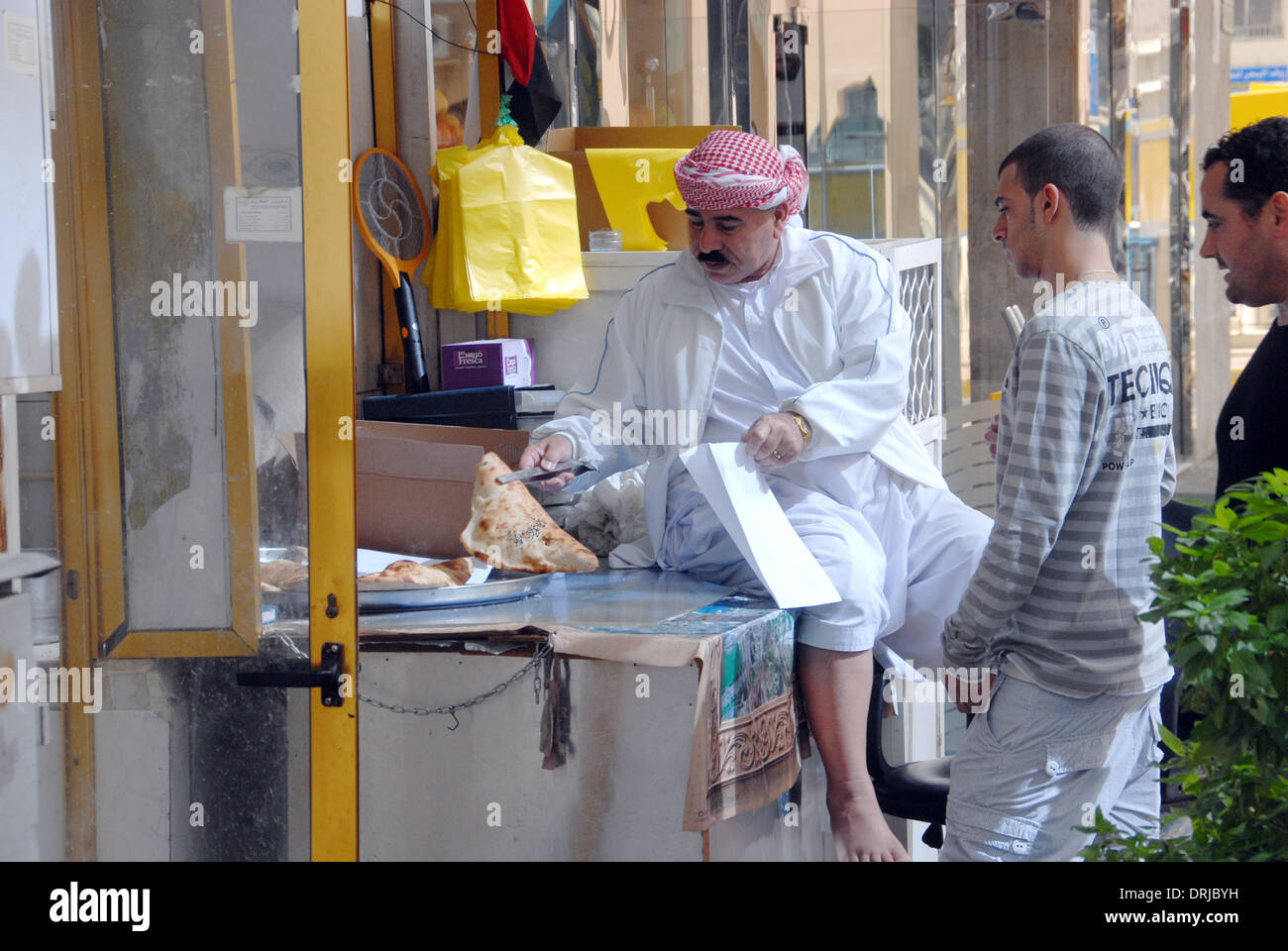 A baker serves some of his customers in Abu Dhabi UAE - Stock Image