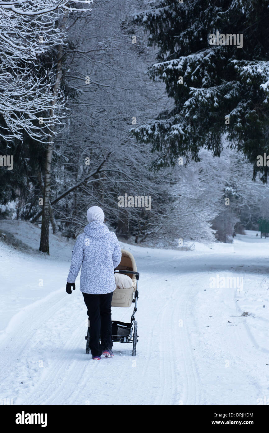 A woman pushes a pram or pushchair in a snowy forest Stock Photo