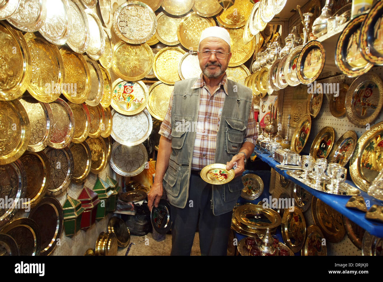 Seller of traditional carved plates that are sold as souvenirs at one of the many souvenir shops in Medina  in Tunis, Stock Photo