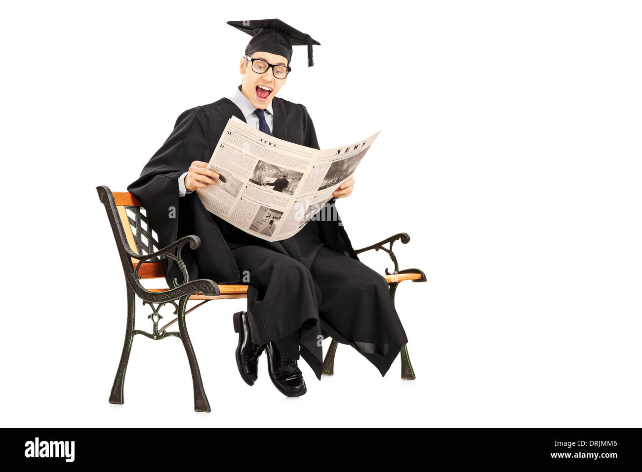 Excited guy in graduation gown reading a newspaper seated on bench - Stock Image