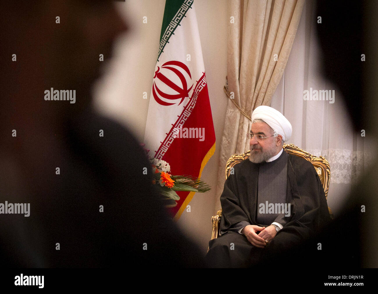 Tehran, Iran. 27th Jan, 2014. Iranian President Hassan Rouhani listens during his meeting with South Korean National Assembly Speaker Kang Chang-hee at presidential palace in Tehran, capital of Iran, on Jan. 27, 2014. Rouhani called for closer economic ties with South Korea here on Monday, semi-official Fars news agency reported. Credit:  Ahmad Halabisaz/Xinhua/Alamy Live News - Stock Image