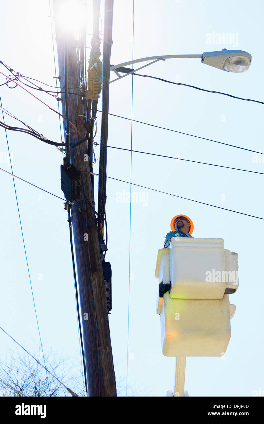 Power engineer riding in lift bucket to work on power lines, Braintree, Massachusetts, USA - Stock Image
