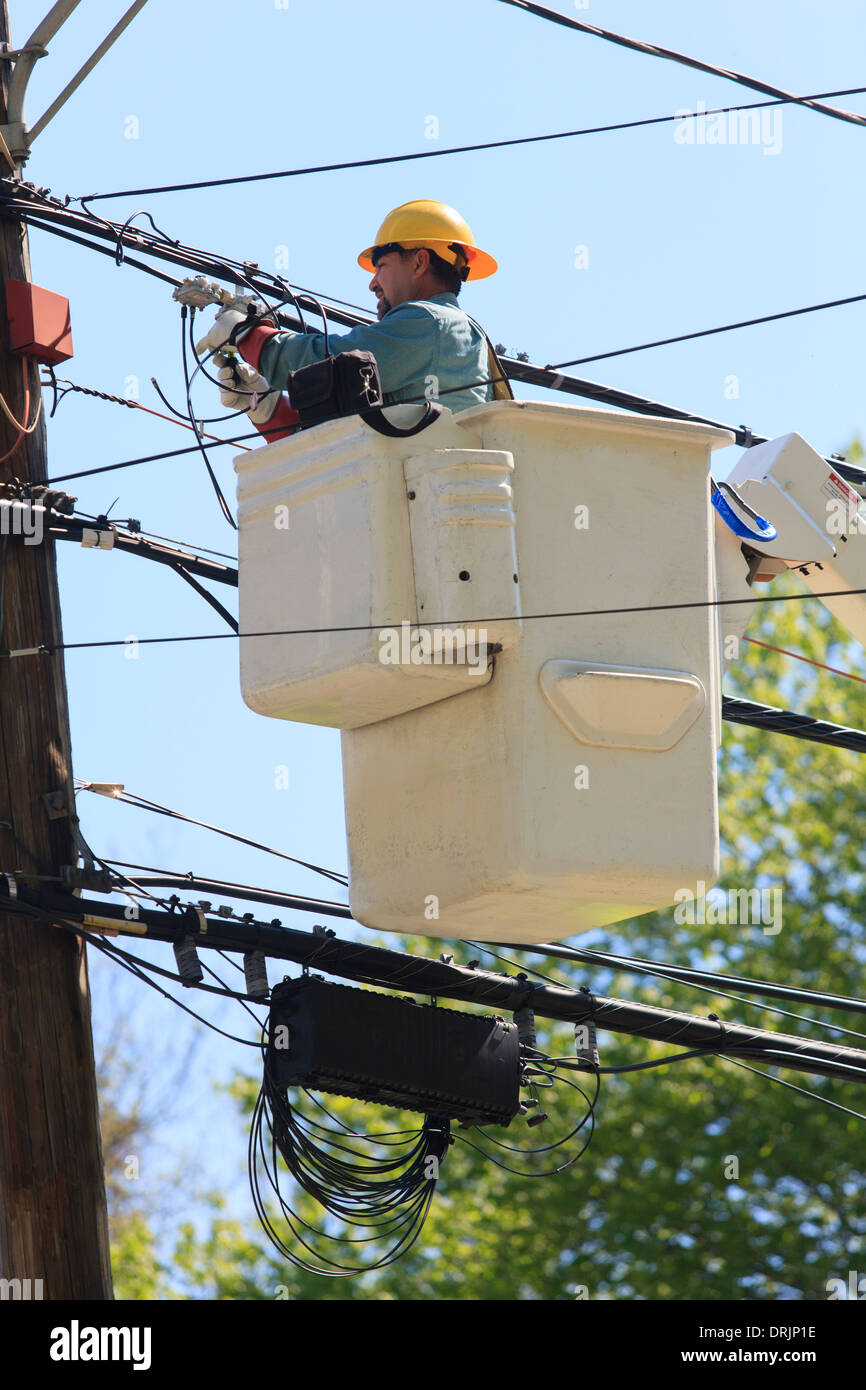 Power engineer in lift bucket working on power lines, Braintree, Massachusetts, USA - Stock Image