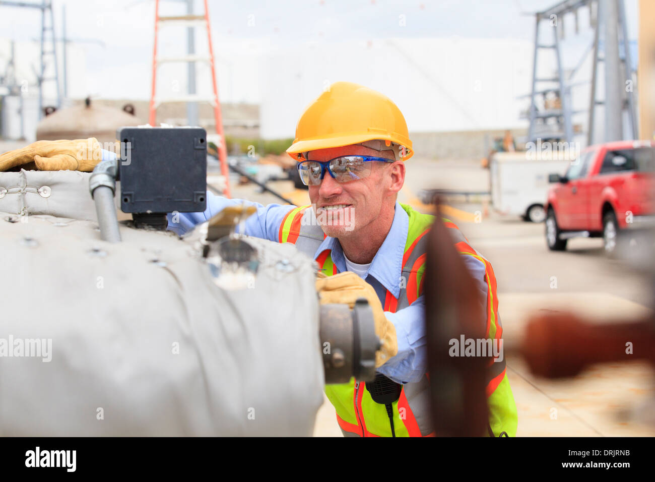 Electrical engineer examining pressure sensor at an electric power plant - Stock Image